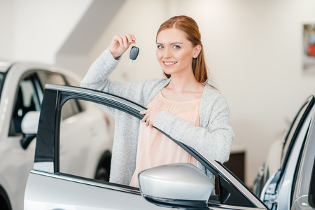 woman holding car key and standing at car in dealership salon