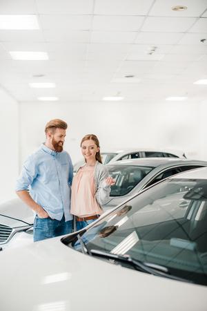 couple choosing car in dealership salon, woman pointing on car