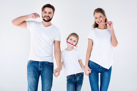 Happy family in white t-shirts cleaning teeth with toothbrushes