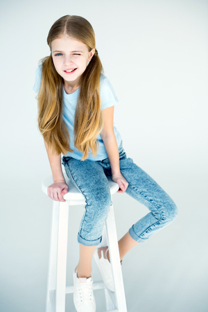 little stylish grimace girl sitting on chair
