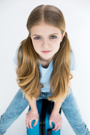 Adorable girl sitting on suitcase and looking at camera in studio