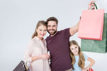 mother, father and daughter standing with shopping bags