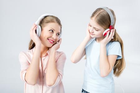 Moeder en dochter luisteren muziek met koptelefoon in studio