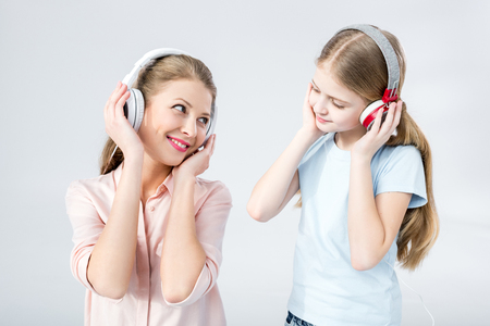 mother and daughter listening music with headphones in studio Imagens
