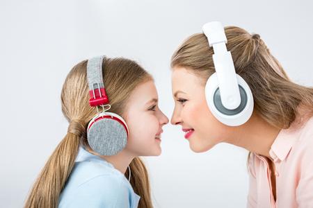 madre e hija escuchando música con auriculares en estudio