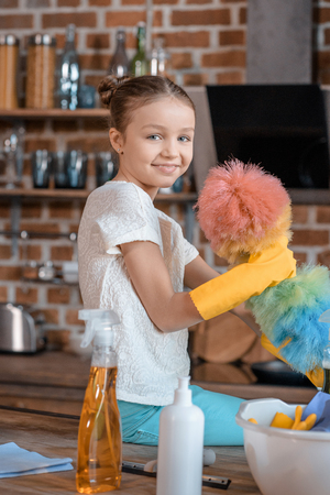 smiling girl in rubber gloves with cleaning supplies in kitchen