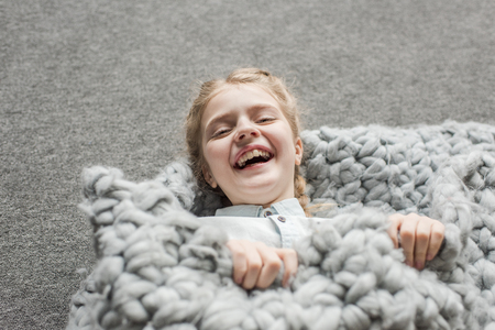 girl laughing and lying on floor with grey knitted blanket