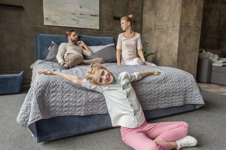 adorable daughter with mother and father relaxing on bed at home