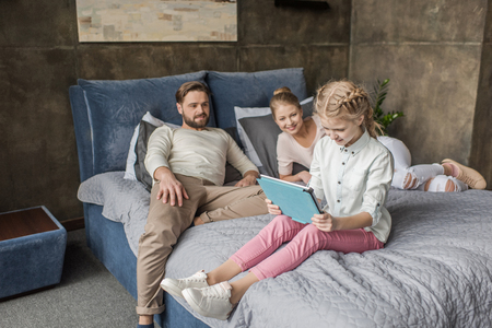 daughter using digital tablet and lying on bed with parents
