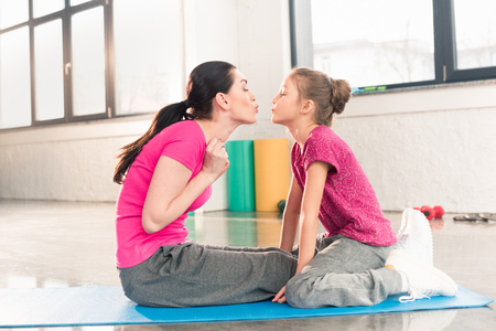 happy mother and daughter sitting on yoga mat and kissing Stock Photo