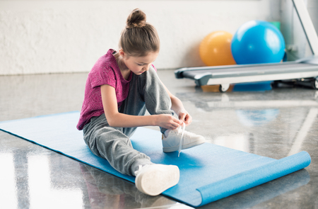 little girl in sportswear sitting on mat and tying shoelace in gym Stock Photo