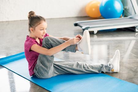 klein meisje in sportkleding zittend op yoga mat en koppelverkoop schoenveter Stockfoto