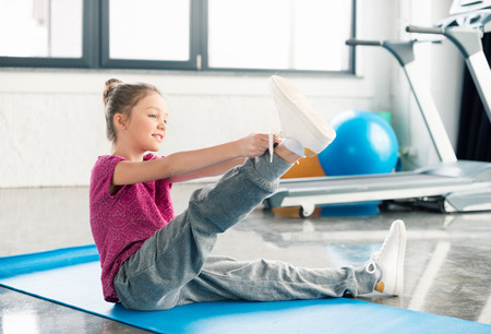 smiling little girl sitting on mat and tying shoelace in gym