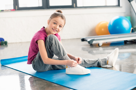 little girl in sportswear tying shoelace and smiling at camera Stock Photo