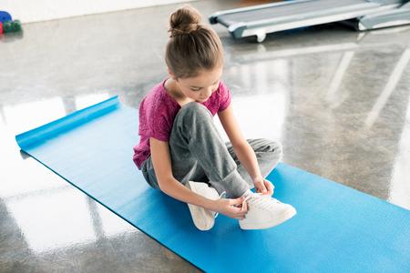 little girl in sportswear sitting on yoga mat and tying shoelace