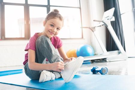 fille en chemise rose, assis sur un tapis de yoga et attacher les lacets dans la salle de gym