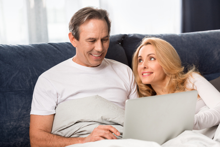 Mitte gealterte Paare, die Laptop verwenden und zu Hause auf Bett liegen Standard-Bild - 77271179