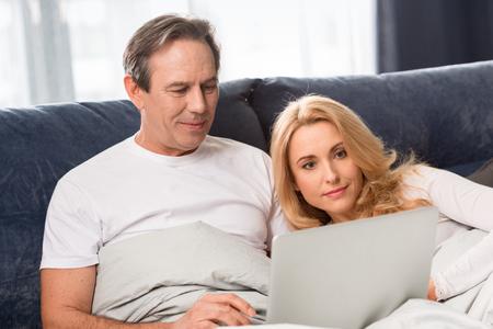 Mitte gealterte Paare, die Laptop verwenden und zu Hause auf Bett liegen Standard-Bild - 77271193