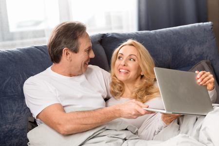 Mitte gealterte Paare, die Laptop verwenden und zu Hause auf Bett liegen Standard-Bild - 77279279