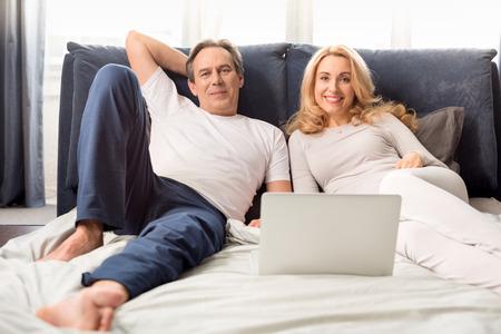 Mitte gealterte Paare, die Laptop verwenden und zu Hause auf Bett liegen Standard-Bild - 77279302