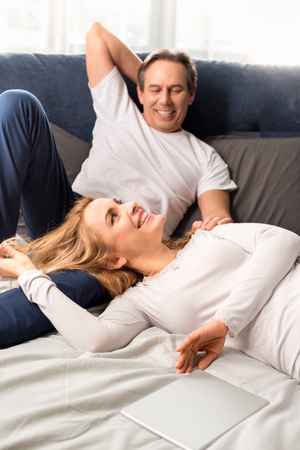 middle aged couple smiling and lying on bed at home
