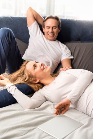 Paar mittleren Alters lächelnd und liegend auf dem Bett zu Hause Standard-Bild - 77278903