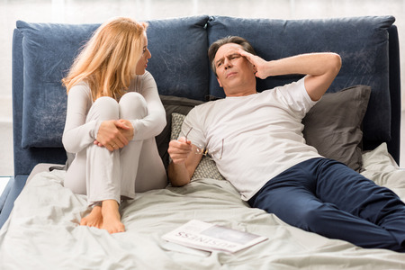 aged couple quarreling and lying on bed at home, man with headache