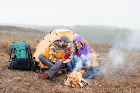 Happy family looking at burning fire Stock fotó