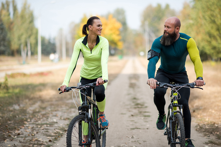 Smiling couple cycling in park Stock Photo
