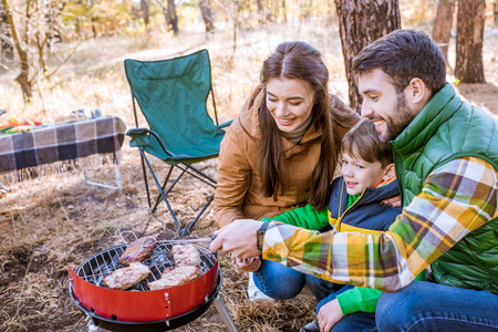 Family grilling meat on barbecue Stock Photo