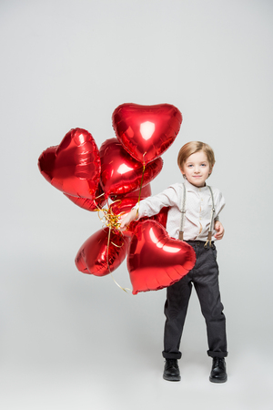 heart shaped: Little boy holding bundle of red heart shaped air balloons on white