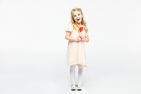 Excited little girl holding heart shaped lollipop and looking at camera on white