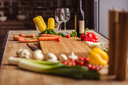 Fresh vegetables, bottle of wine and glasses on kitchen table Stok Fotoğraf