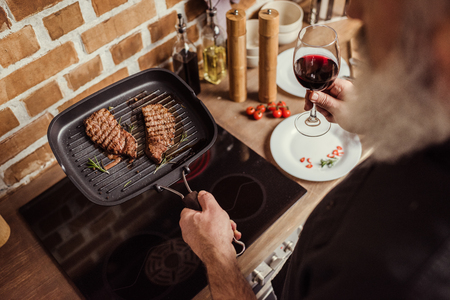View over shoulder of bearded senior man holding grilled steaks and wine glass Stock Photo
