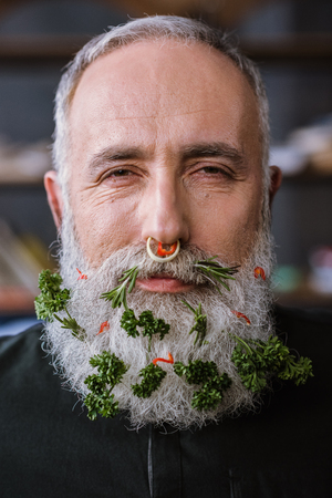 Close-up portrait of senior man with greens in beard smiling at camera Imagens