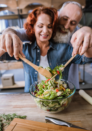 Happy mature couple holding hands and cooking vegetable salad Stock Photo
