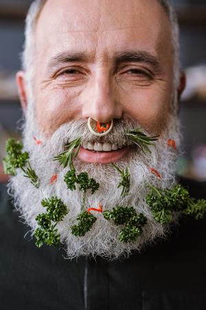 Close-up portret van senior man met groenten in baard glimlachend in de camera