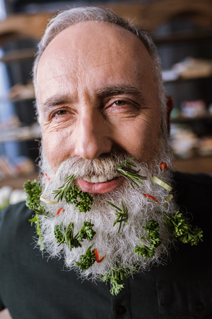 Close-up portrait of smiling senior man with greens in beard