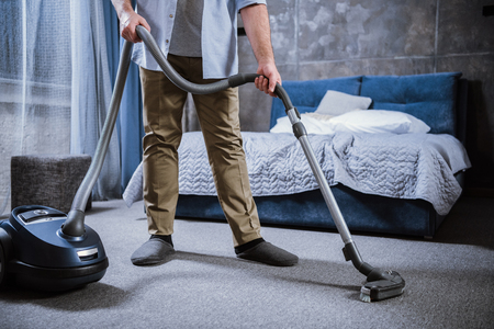 Partial view of man with vacuum cleaner cleaning carpet in bedroom Stock Photo