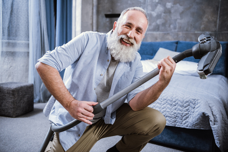 Bearded senior man having fun with vacuum cleaner and smiling at camera Stok Fotoğraf