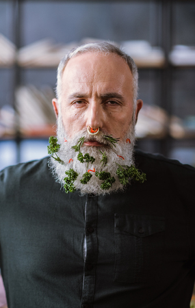 Portrait of serious senior man with vegetables in beard looking at camera