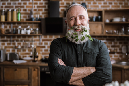 Portrait of confident handsome senior man with greens in beard smiling at camera