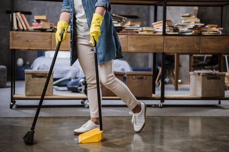 Gedeeltelijke mening van vrouw in handschoenen die vloer met bezem en blik werpen