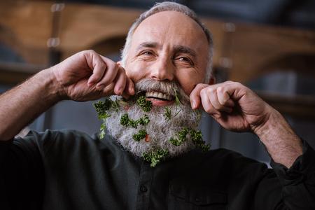 Portret van de glimlachende hogere mens met greens in baard het aanpassen snorren Stockfoto