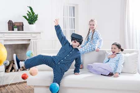 kids in pajamas playing with virtual reality headset at home Фото со стока