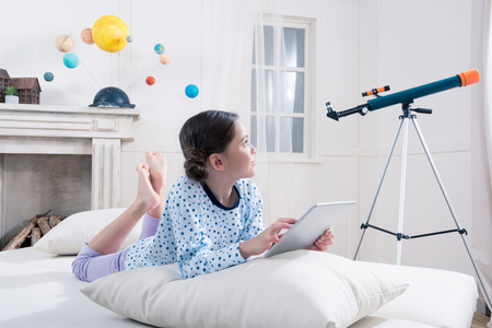 girl in pajamas lying on bed with digital tablet and looking at telescope