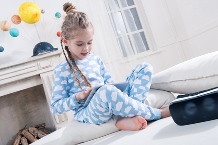 little girl in pajamas using digital tablet