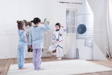 filles saluant un garçon en costume d'astronaute Banque d'images