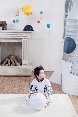 boy in astronaut costume holding helmet, toy rocket behind