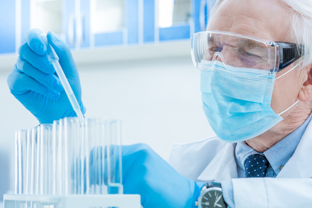chemist with pipette and test tubes in laboratory Imagens
